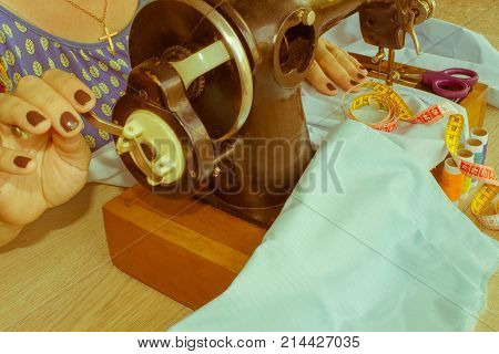Woman hand on sewing machine.Dressmaker work on the sewing machine. Hobby sewing fabric as a small business concept. Female tailor threading leather material on sewing machine poster