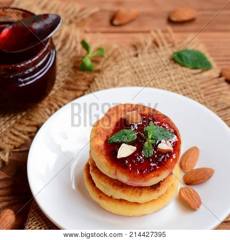 Roasted cottage cheese pancakes with berry jam, almonds and mint on a white plate. Syrniki recipe. Cottage cheese almond flour pancakes