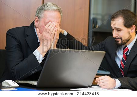 Businessman comforting his depressed and sad boss