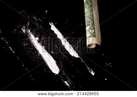 cocaine or other illegal drugs that are sniffed by means of a tube isolated on black glossy background