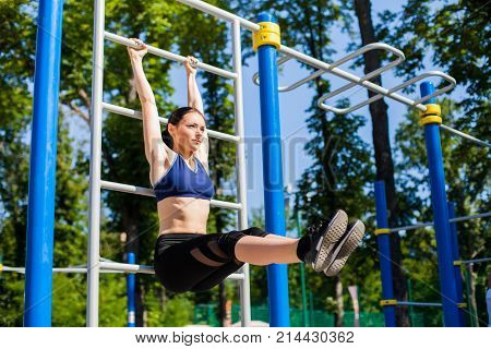 Young athletic female in a bright blue sport bra and black leggings making exercises with horizontal bar on the sport playground. Photo of girl with a beautiful sports body