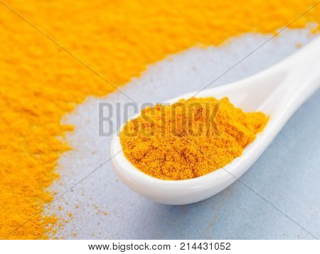 Turmeric Powder or Curcuma longa and white spoon with turmeric powder on gray background. Copy space for text.