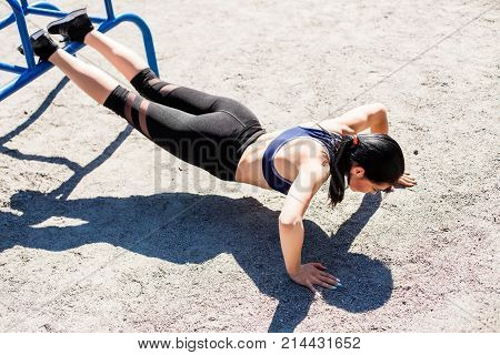 Young sportive teenager in a bright blue sport bra and black leggings doing push ups on the sport playground. Photo of an athlete girl with a beautiful sports body