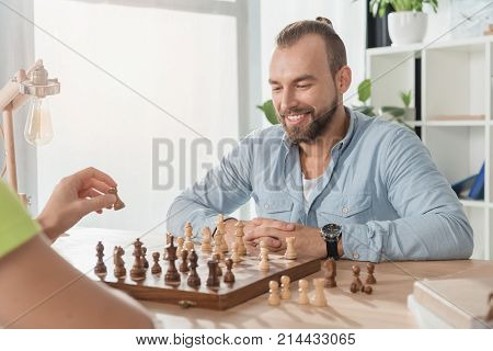 young smiling man playing chess with opponent