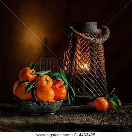 still life with mandarins in the tin bowl and candlelight on wooden background.