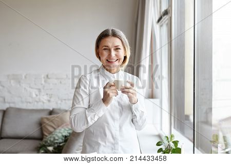 Positive cheerful 60 year old woman medical expert with gathered hair standing by large window in modern apartment interior having coffee break while working from home consulting patients