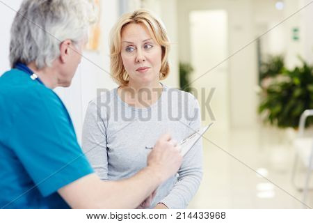 Mid-aged blonde having talk with doctor making prescriptions for her