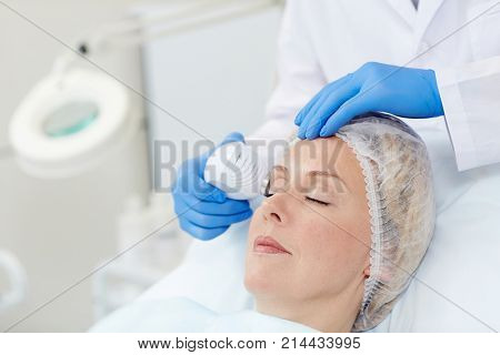 Middle aged woman having anti-age cosmetician procedure on her eyelids