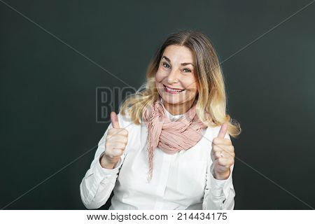 Picture of expressive cheerful middle aged Caucasian female wearing white blouse and pink scarf smiling broadly showing thumbs up gesture at camera satisfied with quality of some product