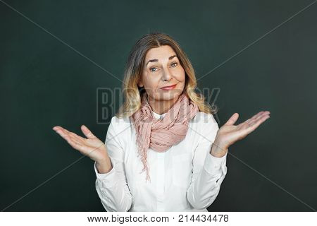 Positive beautiful middle aged European female with charming smile raising hands as if making scale with her arms wide open. Confused senior woman feeling uncertain shrugging her shoulders
