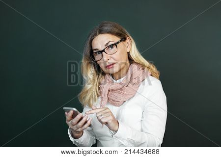 Elderly people age technology and communication concept. Portrait of confident modern senior woman wearing white blouse stylish eyeglasses and pink scarf messaging online using mobile phone