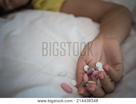 Young woman is lying on the bed with a lot of pills. Overdose and suicide concept.
