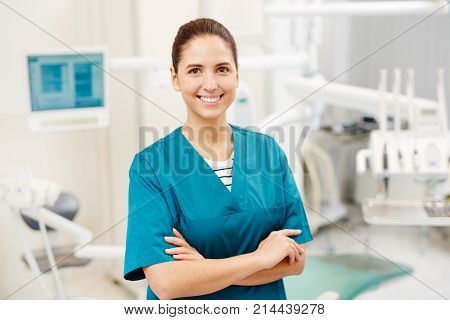 Happy young dentist or surgeon in uniform with crossed arms on her chest