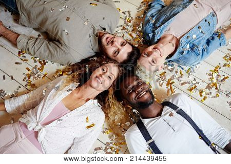 Four intercultural friends lying head to head on the floor covered with confetti