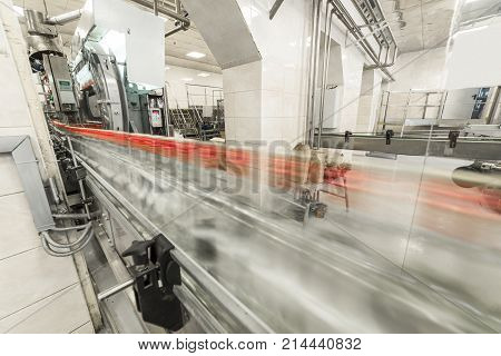 Bottles with vodka on the conveyor. Production and bottling of alcoholic beverages.