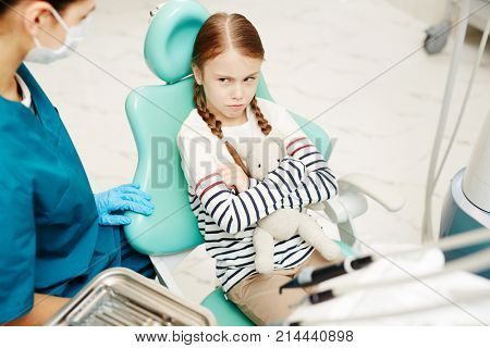Sulky little girl is afraid of dental examination and healing