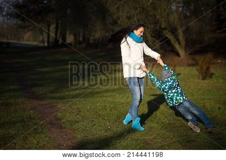 Young woman and boy 9-10 years have fun in the autumn park. Mom holds his son by the hands and turns around with him. A pleasant day a good mood.