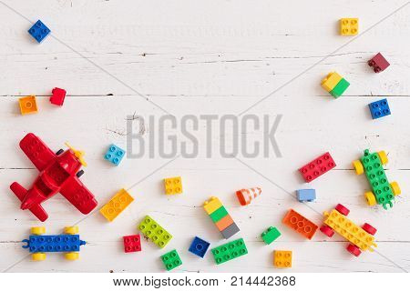 Top view on multi-color toy bricks on white wooden background. Toys in the table.