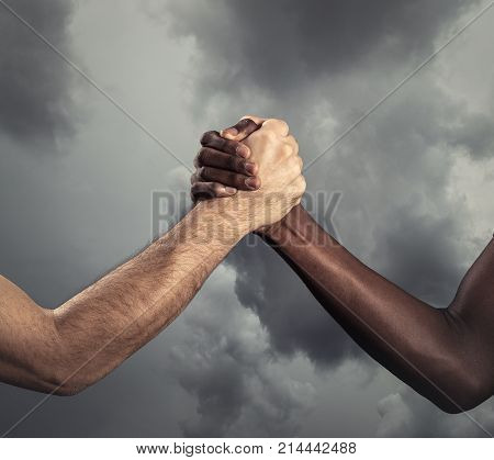 Interracial human hands for friendship - Concept of peace and unity against racism - Multi ethnic people holding hands