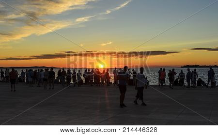 ZADAR, CROATIA - 15 JULY, 2017: People admire the sunset on the beach
