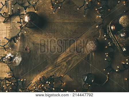 Christmas or New Year background. Holiday preparation flat-lay. Vintage Christmas tree golden toy decoration balls and light garland over rustic wooden background, top view, copy space
