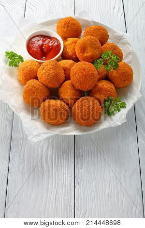 tasty potato croquettes - mashed potatoes balls breaded and deep fried served with ketchup on white plate vertical view from above