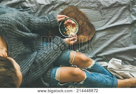 Healthy winter breakfast in bed. Woman in grey sweater and jeans eating rice coconut porridge with figs, berries, hazelnuts, top view, copy space. Clean eating, alkaline diet, comfort food concept