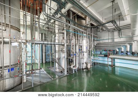 Silvery distillation columns entangled in a multitude of pipes, valves and sensors. Manufacture of alcohol.