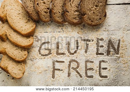 Sliced pieces of bread on the top of wooden table with flour, gluten free concept. Homemade gluten free bread for people with allergy.