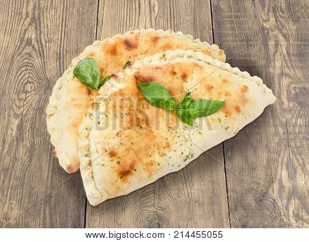 Two baked calzone - closed type of pizza that is folded in half decorated with basil twigs on an old rustic wooden surface