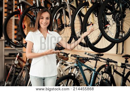 A salesman in a bicycle shop poses near a bicycle. There are parts, different types of bicycles. She smiles at the camera.