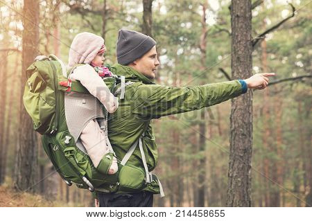 father with baby in child carrier on a hike in the woods