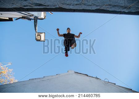 Young man doing impressiveparkour jump from one roof to another.