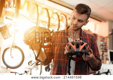 A young man looks closely at the helmets for bicycle rides. He came to the bicycle shop for shopping. He chooses from different goods.