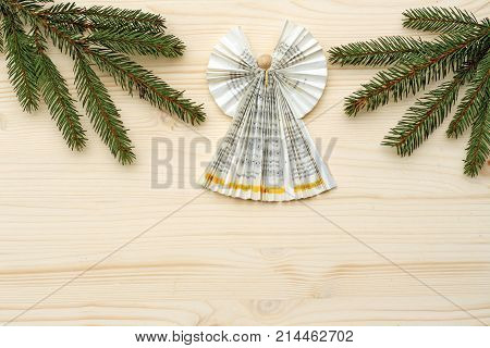 Christmas background angel folded with paperfrom a church songbook and spruce branches