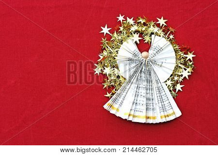 angel folded of paper with a wreath of goden stars on red cloth