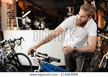 The seller in the bicycle shop holds the bicycle handlebars. Around him there are many parts for bicycles.