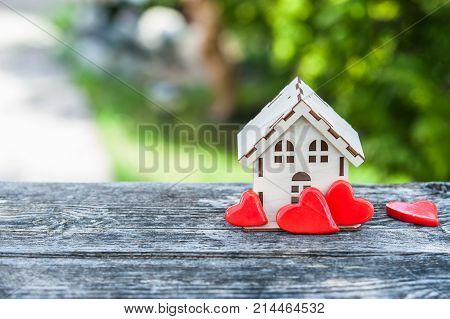 A toy house with a fence of hearts. A symbol of a house where love reigns. Theme of happiness warmth good luck love construction travel hotel business family