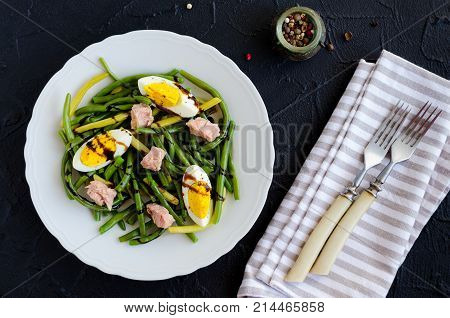 Fresh summer warm salad with cooked green beans tuna boiled eggs and sauce balsamico glassa in white plate on black stone background. Healthy eating concept. Top view.
