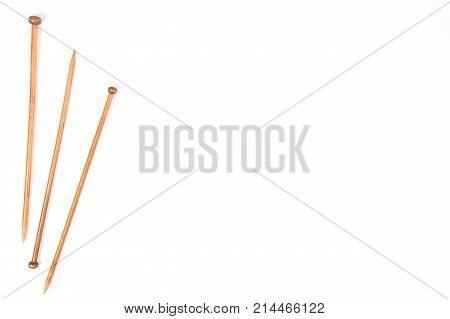 Wooden knitting needles on white background. Top view, copy space for text