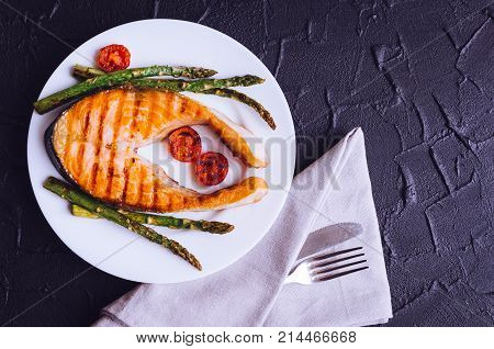 Grilled salmon steak with asparagus and tomatoes cherry on a white plate on black stone background. Healthy lunch concept. Delicious nutritious eating. Top view. Copy space.