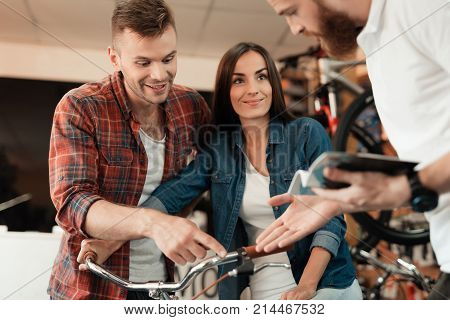 A young couple came to the bicycle shop to choose a new bicycle. A man and a woman look attentively at different bicycles and details. The consultant helps them.