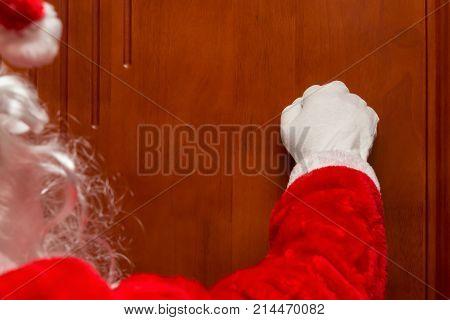 Santa Claus knocking the door horizontal composition