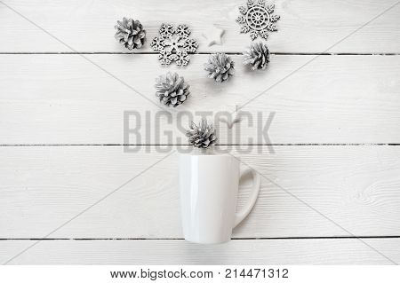 Mockup white mug with christmas cones and stars, on a white wooden background. Flat lay, top view photo mock up.