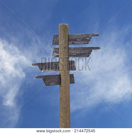Old Wooden Road Sign With Four Arrows Over Sky