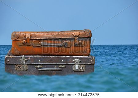 Vintage Travel Suitcases Flaot In Blue Sea Water