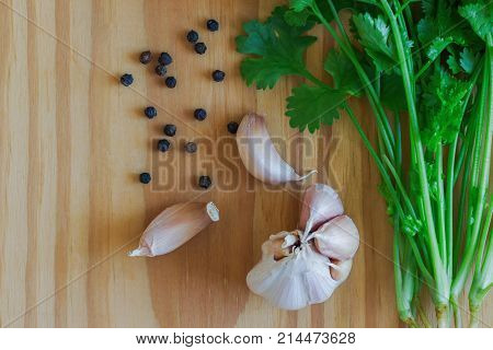 Green leaves coriander garlic and black pepper put on wooden table in top view flat lay with copy space. Food preparation concept for fresh vegetable and spices.Cilantro or coriander with black pepper and garlic for seasoning.