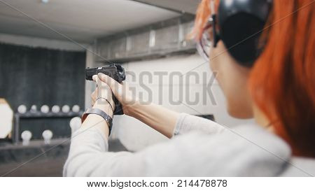 Woman shooting with a gun in shooting gallery, close up