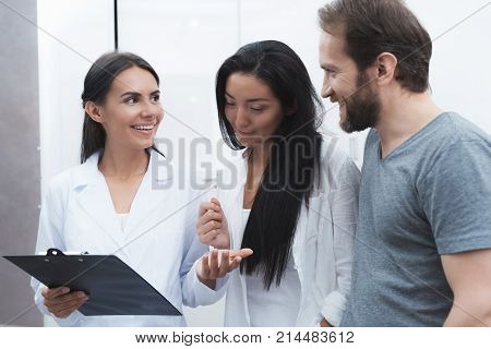 A man and a woman came to see a dentist. They were met by the receptionist, he shows them the information on the form. All of them look at the form and smile.