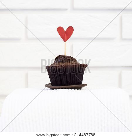 Chocolate muffin with a red heart. Valentine's Day concept. Sweet gift to the beloved